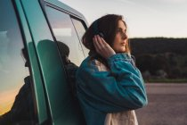 Замислений жінка в навушниках, спираючись на автомобіль — стокове фото