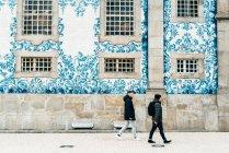Touristes masculins marchant au mur décoré de carreaux blancs et bleus, Porto, Portugal — Photo de stock