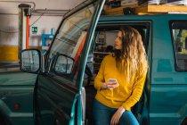 Mujer con smartphone mientras que apoyado en el coche en el garaje - foto de stock
