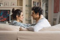 Happy young man and woman looking at each other and sitting on couch at home — Stock Photo