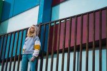 Hübsche blonde Frau steht am Zaun gegen bunte moderne Häuser — Stockfoto