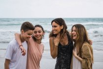Portrait of woman and teenagers standing and talking on seashore — Stock Photo