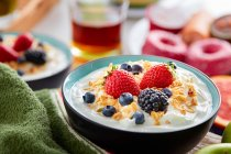 Bowl of fresh yogurt topped with berries and cornflakes — Stock Photo