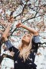 Giovane donna bionda con gli occhi chiusi in piedi all'albero in fiore con le mani in alto — Foto stock