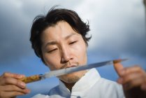 Japanese chef checking knife in front of blue sky — Stock Photo