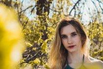 Портрет молодой девушки, стоящей в кустах со свежими побегами весенних листьев — стоковое фото