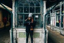 Man stützte sich auf trashigen Holzfenster während der Verwendung der Kamera in der alten Stadt Street, Porto, Portugal — Stockfoto