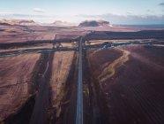 Carretera en terreno sombrío y montañas en el fondo, Islandia - foto de stock