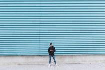 Joven adolescente de pie en la pared del metal y el uso de smartphone - foto de stock