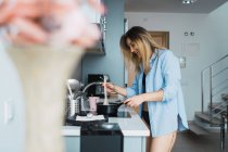 Laughing young woman in shirt preparing food in saucepan in kitchen — Stock Photo