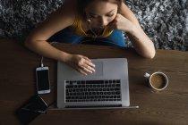Mulher usando o laptop na mesa com o copo e smartphone — Fotografia de Stock