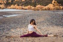 Femme en forme assis et étirant dans la pose de ficelle sur le rivage à l'océan — Photo de stock