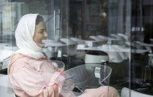 Lachende Marokkanerin mit Hijab und typisch arabischem Kleid sitzt im Café — Stockfoto