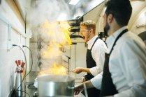 Aufgeregter Koch kocht in Restaurantküche mit Kollegen Flammkuchen — Stockfoto