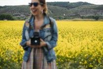 Mulher óculos de sol rindo na natureza, mantendo a câmera retro — Fotografia de Stock