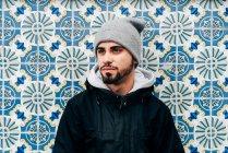 Retrato de turista masculino pensativo em pé na parede com azulejos azuis — Fotografia de Stock
