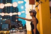 Élégante jeune femme asiatique, debout sur la rue et capture cab en soirée — Photo de stock