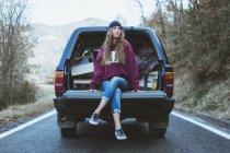 Giovane donna premurosa seduta sul bagagliaio della macchina nella foresta — Foto stock