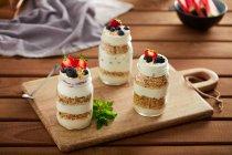 Vasi di vetro con muesli e yogurt su tavola di legno — Foto stock