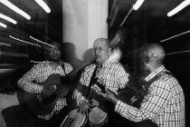 Музичне тріо Куби грає в нічному клубі, чорно-білий постріл з довгим виступом. — стокове фото
