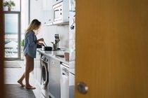 Joven alegre sensual haciendo el desayuno en la cocina - foto de stock