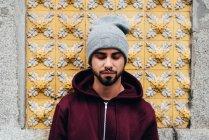 Retrato de Bonito jovem de pé na parede com azulejos amarelos — Fotografia de Stock