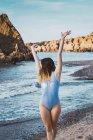Jovem mulher em traje de banho andando na praia com braços erguidos — Fotografia de Stock
