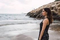 Елегантний вдумливі жінка, стоячи на пляж і, дивлячись на вид — стокове фото