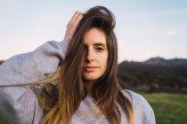 Jolie jeune femme regardant la caméra et de toucher la tête dans la nature — Photo de stock