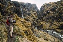 Homme barbu avec sac à dos et les commandes de la caméra dans les montagnes près de petite cascade et rivière — Photo de stock