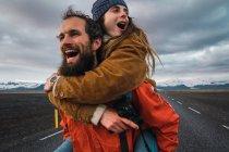 Бородатий чоловік жінка на назад під керуванням і сміятися на порожній дорога біля гори — стокове фото