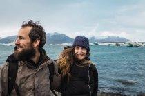 Hombre barbudo y mujer riendo en ropa de abrigo en el fondo del mar frío en Islandia - foto de stock