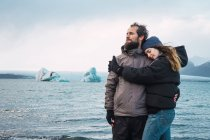 Loving embracing couple standing on cold seascape — Stock Photo