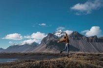 Ragazza emozionante che salta sulla costa con montagne sullo sfondo, Islanda — Foto stock
