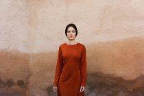 Mulher em pé contra a parede marrom — Fotografia de Stock