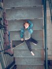 Boy lying with skateboard on stairs — Stock Photo