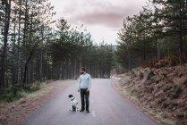 Homem com pé de cachorro na estrada — Fotografia de Stock