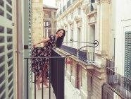 Женщина, стоя на балконе в городе — стоковое фото