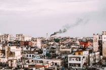 Старий пошарпаний міської забудови та будинки з Чорний дим на фоні, Куби — стокове фото