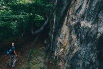 Escalador en el acantilado en el bosque - foto de stock
