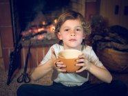 Мальчик, сидя у камина с чашкой — стоковое фото