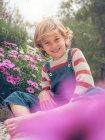 Ragazzo biondo che si siede nel giardino — Foto stock