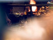 Cropped view of unrecognizable glassblower working on factory and making glass decoration. — Stock Photo