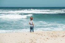 Мальчик, стоя на пляже — стоковое фото