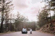Homem com cão sentado na estrada — Fotografia de Stock