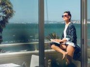 Mujer joven relajándose con libro en el balcón junto al mar . - foto de stock