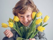 Elementary age boy with yellow tulips in jug looking in camera. — Stock Photo