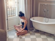 Woman meditating at window — Stock Photo