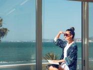 Mujer joven relajándose con libro y mirando a la vista en el balcón junto al mar . - foto de stock