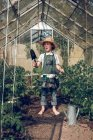 Boy standing in greenhouse with shovel — Stock Photo